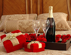 Picture of wine glasses and a wine bottle on a bed.